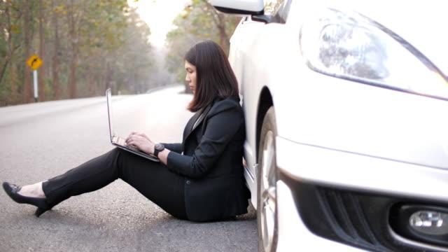 vídeos y material grabado en eventos de stock de mujer que trabaja en el camino para enviar correo electrónico al cliente porque el desglose del coche - imperfección