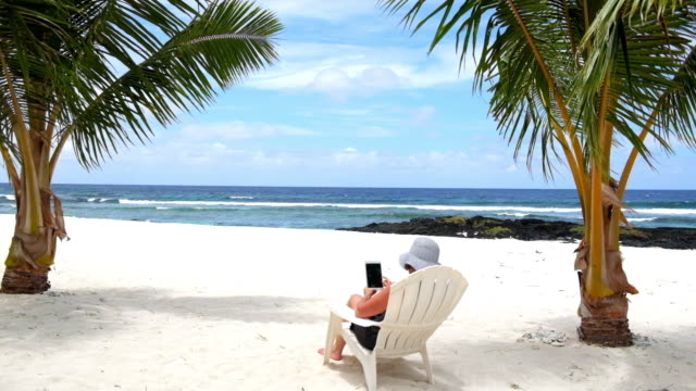 Woman working on vacation sitting on tropical beach under palm trees on deck chair using and typing on a tablet in portrait orientation video