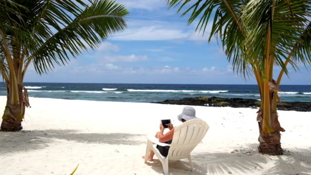 Woman working on vacation sitting on tropical beach under palm trees on deck chair using and typing on a tablet in landscape orientation video