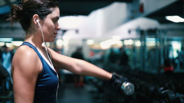 Woman working out her arms at gym with weights video
