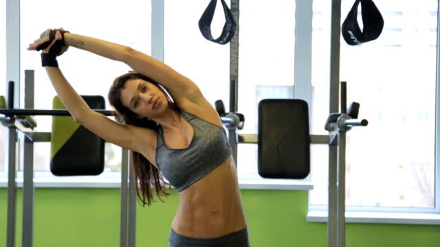 Woman working out in gym warming up her upper body and hands. Healthy lifestyle concept video