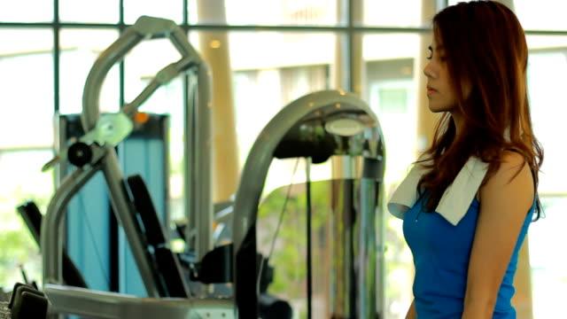 stockvideo's en b-roll-footage met vrouw uit te werken in de sportschool - bankdruktoestel