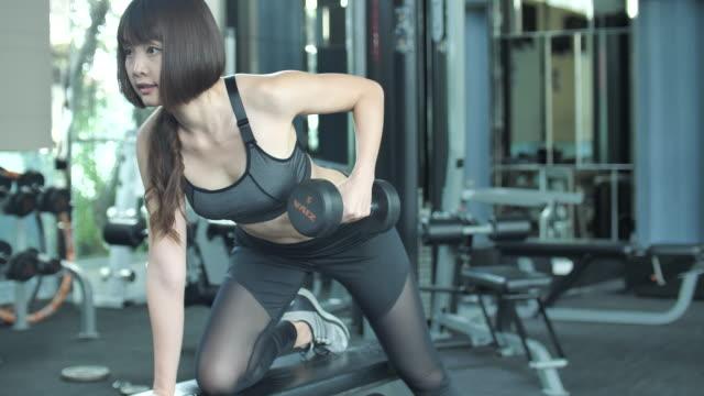stockvideo's en b-roll-footage met vrouw uit te werken in de sportschool met dumbbell - bankdruktoestel