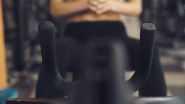 Woman working out on a exercise machine at the gym Woman working out at the gym, she is grabbing handles on a exercise machine, hands close up, sports and fitness concept gripping stock videos & royalty-free footage