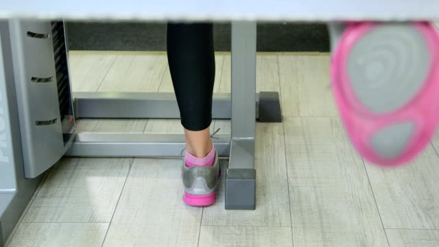 Woman working out on standing leg curl machine in fitness club closeup video