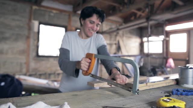 bir testere ile çalışan kadın - döner lamalı testere stok videoları ve detay görüntü çekimi