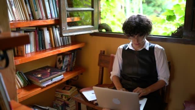 stockvideo's en b-roll-footage met vrouw werkt/studeert met laptop voor een boekenplank thuis - boekenkast