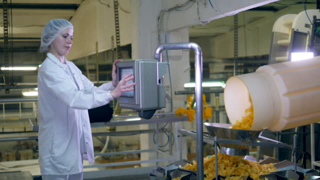 Woman works with a factory machine, controlling a conveyor with chips. Woman works with a factory machine, controlling a conveyor with chips. HD prepared potato stock videos & royalty-free footage