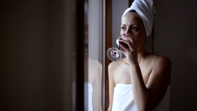 Woman, wrapped in a towel, drinking wine Young woman, wrapped in towel, is standing by the window and drinking red wine. wearing a towel stock videos & royalty-free footage