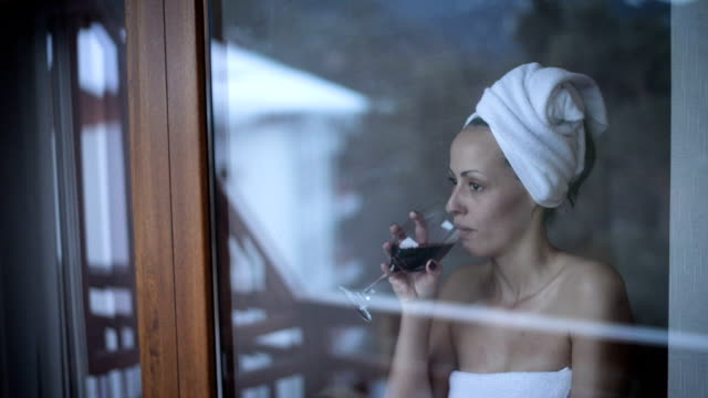 Woman, wrapped in a towel, drinking wine video
