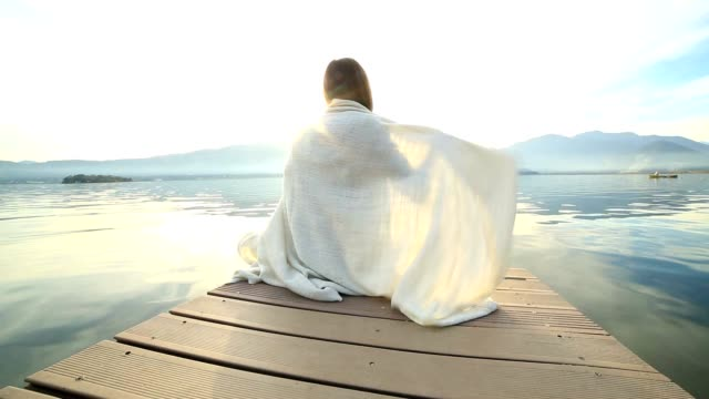 Woman wrapped in blanket on wooden jetty video