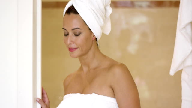 Woman wrapped in towel leaving shower stall Beautiful single young grinning woman leaving a shower or bathroom with body and hair wrapped in towel wearing a towel stock videos & royalty-free footage