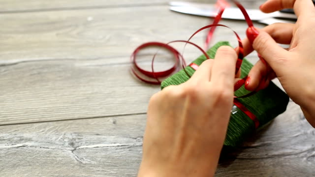 Woman wrapping modern Christmas gifts presents at home video
