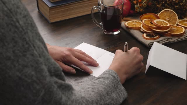 Woman writes Christmas greetings on a greeting card. Close up