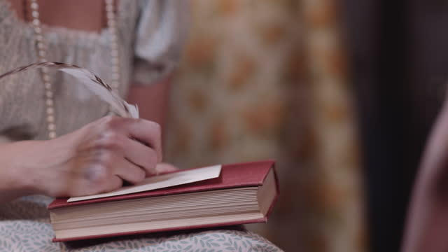 Woman writes with quill in period costume.