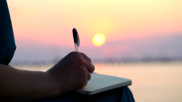 Woman writing in her diary at sunset video