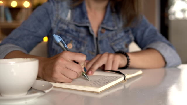Woman writing in journal, diary video