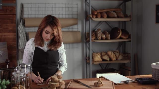 vidéos et rushes de femme écrivant des ingrédients pour le pain frais, elle fait en boulangerie - boulanger