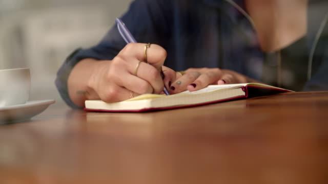 diario di scrittura donna a sedere finestrino nel caffè negozio - to do list video stock e b–roll