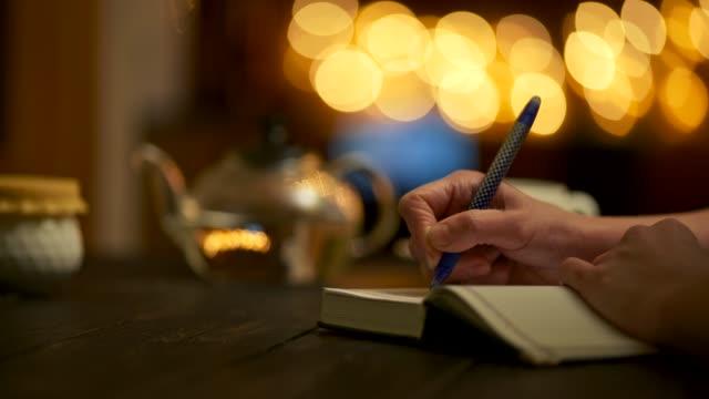 vídeos de stock, filmes e b-roll de mulher escrevendo notas em seu livro de notas usando caneta. mantendo seu diário, anunciando criativos, escrevendo poesias e novas receitas alimentares. tiro panorâmico, 4k - escrever