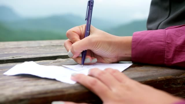 Woman writing on a notepad using a pen