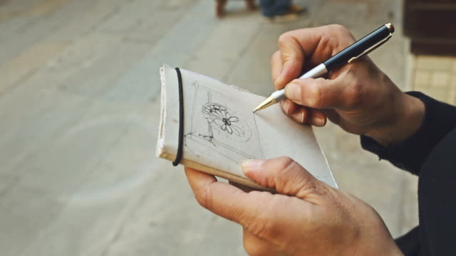 Woman writing on sketchbook architectural details video