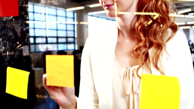 Woman writing on sticky notes video