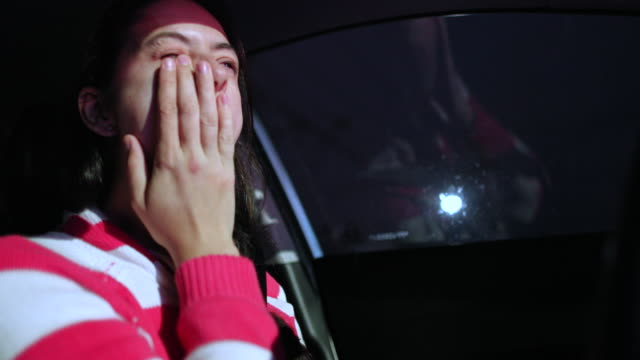 Woman yawning while driving at night. Tired female driver putting hand in mouth