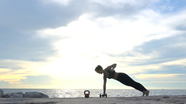 Woman Yoga on the beach at sunset
