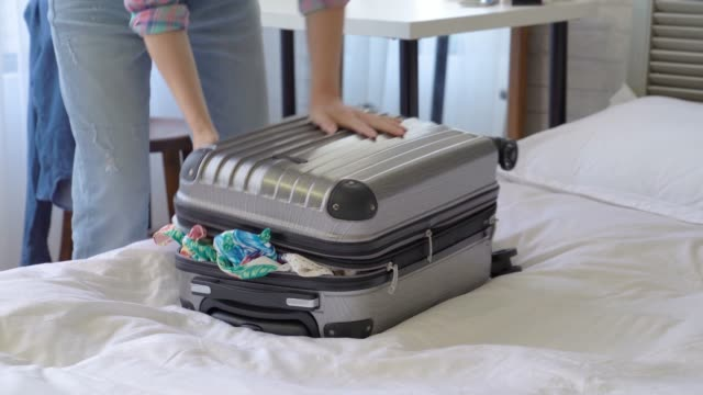 woman zipped the suitcase with all her strength
