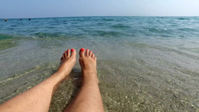 Womans bare feet on a beach splashed by waves, summer travel concept background, 4k Womans bare feet on a beach splashed by waves, summer travel concept background, 4k sunbathing stock videos & royalty-free footage