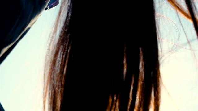 Kvinnans brunett hår vajande från vind på naturen under gyllene solnedgång video