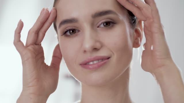 woman's face care. smiling female touching skin on face - viziarsi video stock e b–roll