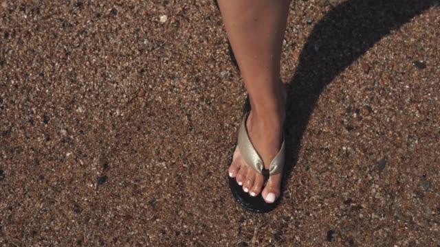 Woman's feet in sandals on beach.