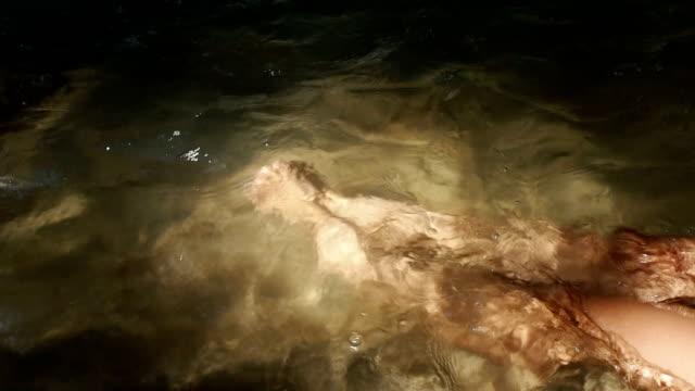 Woman's feet in waterfall video
