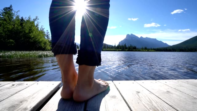woman's feet on jetty above lake at sunrise, canada- 4k - molo video stock e b–roll