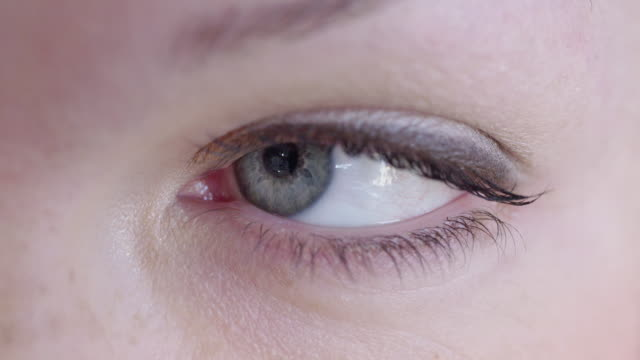 Woman's grey eye looking at camera video