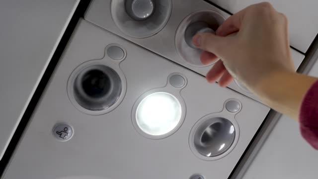 kvinnans hand justerar ventilation och stänger av ljuset ovanför sätet på planet - kvinna ventilationssystem bildbanksvideor och videomaterial från bakom kulisserna