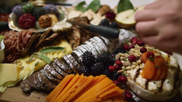 a woman's hand arranges sprigs of thyme around an appetizer charcuterie meat/cheeseboard with various fruit, sauces, and garnishes on a table at an indoor celebration/party - taca filmów i materiałów b-roll