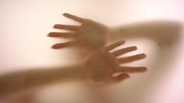 Woman's hand behind fogged glass