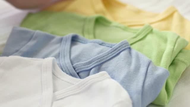 hd: mano di donna delicata capi baby - abbigliamento da neonato video stock e b–roll
