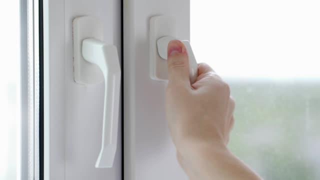 en kvinnas hand stänger fönstret i köket - kvinna ventilationssystem bildbanksvideor och videomaterial från bakom kulisserna