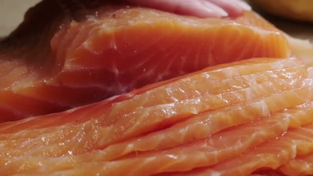 a woman's hand cuts fresh salmon by slices. close-up cutting board with red fish on the table. - articoli casalinghi video stock e b–roll