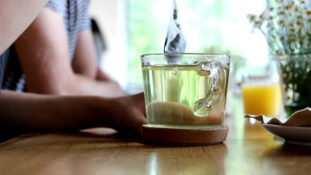 woman's hand dipping teabag in cup at cafe - tea cup stock videos & royalty-free footage