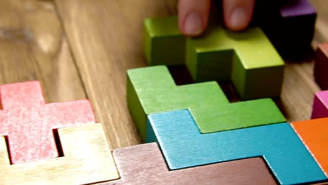 la mano della donna piega blocchi di legno colorati sullo sfondo del tavolo marrone, primo piano, pan shot. il concetto di business. - ucraina video stock e b–roll