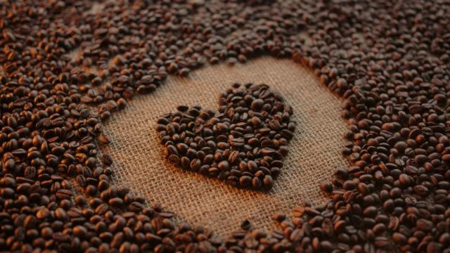 vídeos de stock e filmes b-roll de woman's hand form heart shape illustration made of roasted arabica coffee grains - coração fraco