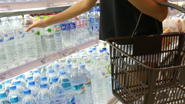 woman's hand fresh water in retail store - prodotti supermercato video stock e b–roll