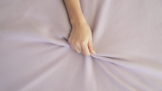 Woman's hand grabbing bed sheet. Pleasure in bed