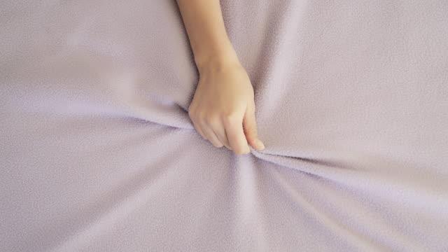 kadın elini tutup çarşaf. yatakta zevk - yatmak stok videoları ve detay görüntü çekimi