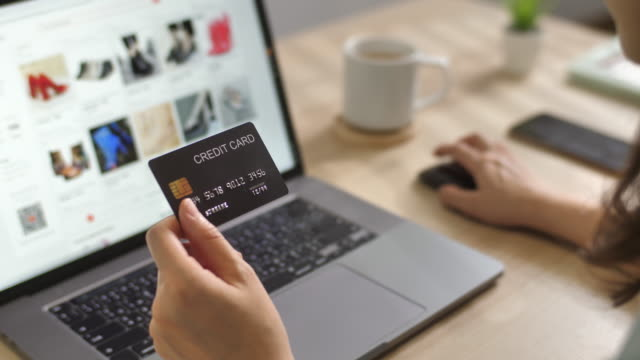 Woman's hand holding a credit card making Shopping online payment for purchase in online website store on Laptop computer